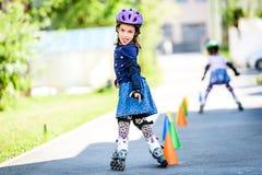 Barn som lär till rullskridskon på vägen med kottar Arkivfoton