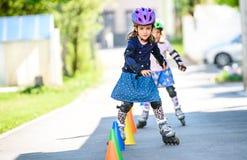 Barn som lär till rullskridskon på vägen med kottar Royaltyfria Bilder