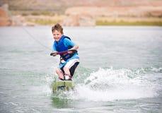 barn som lärer till wakeboarden royaltyfria foton
