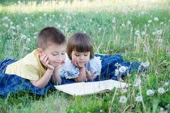 Barn som läseboken parkerar in att ligga på magen som är utomhus- bland maskrosen parkerar in, gulliga barn utbildning och utveck Royaltyfri Fotografi
