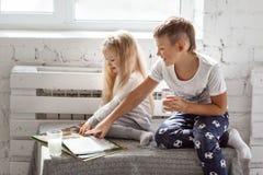 Barn som läser en bok och dricker, mjölkar Royaltyfri Foto