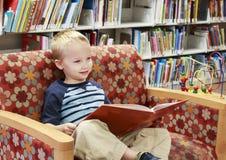Barn som läser en bok på en soffa på arkivet arkivfoton