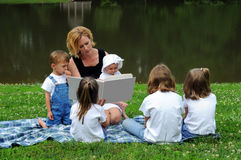 barn som läser till kvinnan Fotografering för Bildbyråer