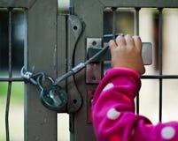 Barn som låsas upp bak ett staket royaltyfri foto