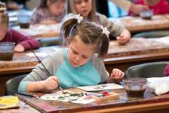 Barn som åldras 6-9 år, deltar i det fria teckningsseminariet under den öppna dagen i vattenfärgskola Fotografering för Bildbyråer