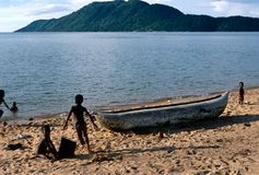 Barn som leker bredvid en pirogue, Lake Malawi. Arkivbilder