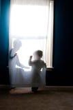 Barn som leker i gardin i fönster Royaltyfria Foton