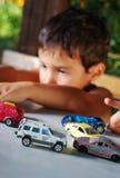 Barn som leker med bilar, toys utomhus- i sommar Royaltyfri Foto