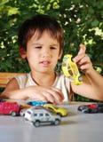 Barn som leker med bilar, toys utomhus- i sommar Royaltyfri Bild