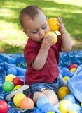 Barn som leker med bollar i trädgård Arkivbild