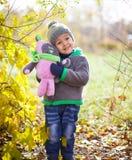 Barn som leker med den fallna hösten, låter vara i park Royaltyfri Fotografi