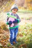 Barn som leker med den fallna hösten, låter vara i park Royaltyfria Foton