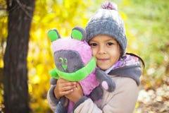 Barn som leker med den fallna hösten, låter vara i park Arkivfoton