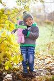 Barn som leker med den fallna hösten, låter vara i park Arkivbilder