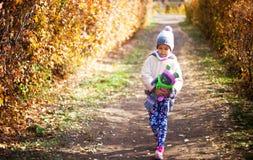 Barn som leker med den fallna hösten, låter vara i park Arkivfoto