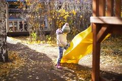 Barn som leker med den fallna hösten, låter vara i park Arkivbild
