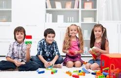 Barn som leker med kvarter Arkivbild