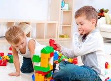 Barn som leker på golvet arkivfoto