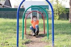 barn som leker utomhus Pojke på lekplatsen, barnaktivitet Aktiv sund barndom Royaltyfri Fotografi
