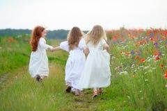 barn som leker utomhus Tre flickor kört avlägsna Royaltyfria Bilder