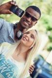 Barn som ler blandras- par som tar foto vid smartphonen Fotografering för Bildbyråer
