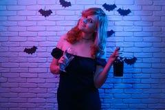 Barn som ler den gladlynta kvinnan med en flaska av vin och ett exponeringsglas fotografering för bildbyråer
