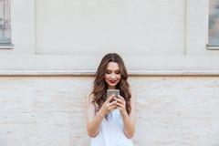 Barn som ler den härliga flickan som utomhus använder hennes telefon arkivfoto