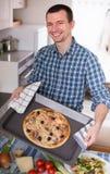Barn som ler den lyckliga mannen som poserar med läcker pizza i kök a royaltyfri fotografi