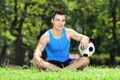 Barn som ler den manliga idrottsman nen som ner sitter på gräs med bollen i a Arkivfoton