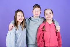 Barn som ler framsidor p? violett bakgrund V?nkram Barns dag Gladlynt ungdom F?rbindelse och kamratskap Lyckligt royaltyfria foton