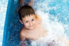 Barn som ler i simbassängen royaltyfria foton
