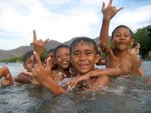 Barn som ler och leker i vattnet Arkivbild