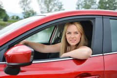 Barn som ler, och tillfredsställd blond flicka i röd bil arkivfoton