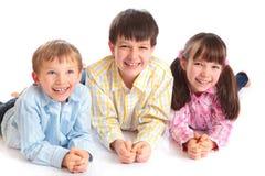 barn som ler tre fotografering för bildbyråer