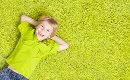 Barn som ligger över grön matta Lycklig le ungepojke arkivbilder