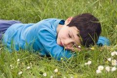 Barn som ligger i gräs Fotografering för Bildbyråer