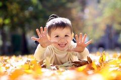 Barn som ligger på den guld- leafen Fotografering för Bildbyråer