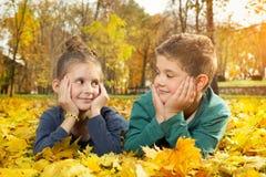 Barn som ligger på den guld- leafen Royaltyfri Fotografi