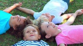 Barn som ligger på gräs och att le stock video