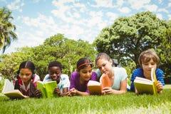 Barn som ligger på gräs och läseböcker Arkivfoton