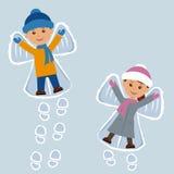 Barn som ligger på snö som snöänglar semestrar nytt år Arkivbilder