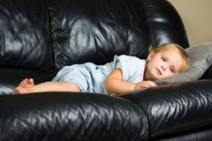Barn som ligger på soffan Royaltyfri Fotografi