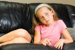 Barn som ligger på soffan Arkivbild