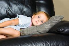 Barn som ligger på soffan Fotografering för Bildbyråer