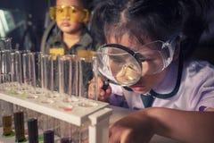 Barn som lutar om kemi i vetenskapsundersökningslaborato arkivfoton