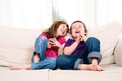 Barn som lyssnar till musik Arkivfoto
