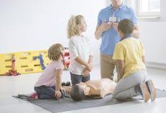 Barn som lyssnar till personen med paramedicinsk utbildning Arkivbilder