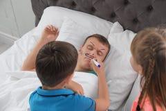 Barn som målar deras faders framsida medan honom som sover fotografering för bildbyråer