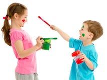 Barn som målar framsidor med ungemålarfärgborstar Royaltyfria Foton