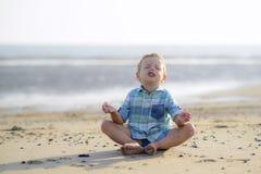 Barn som mediterar på stranden Royaltyfri Foto